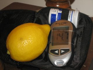 Lemon beside glucometer with reading of 14.7 mmol/L.